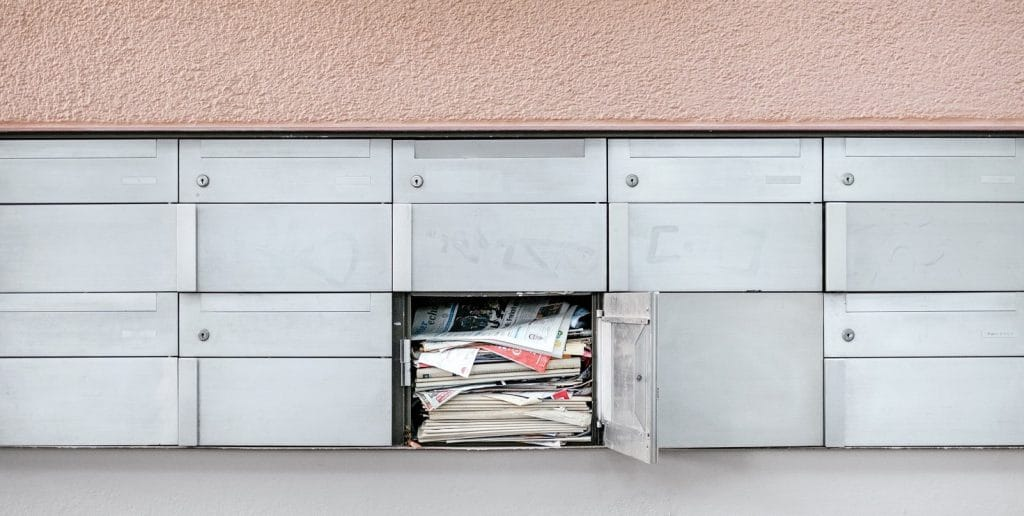an image of a mailbox stuffed with newsletters