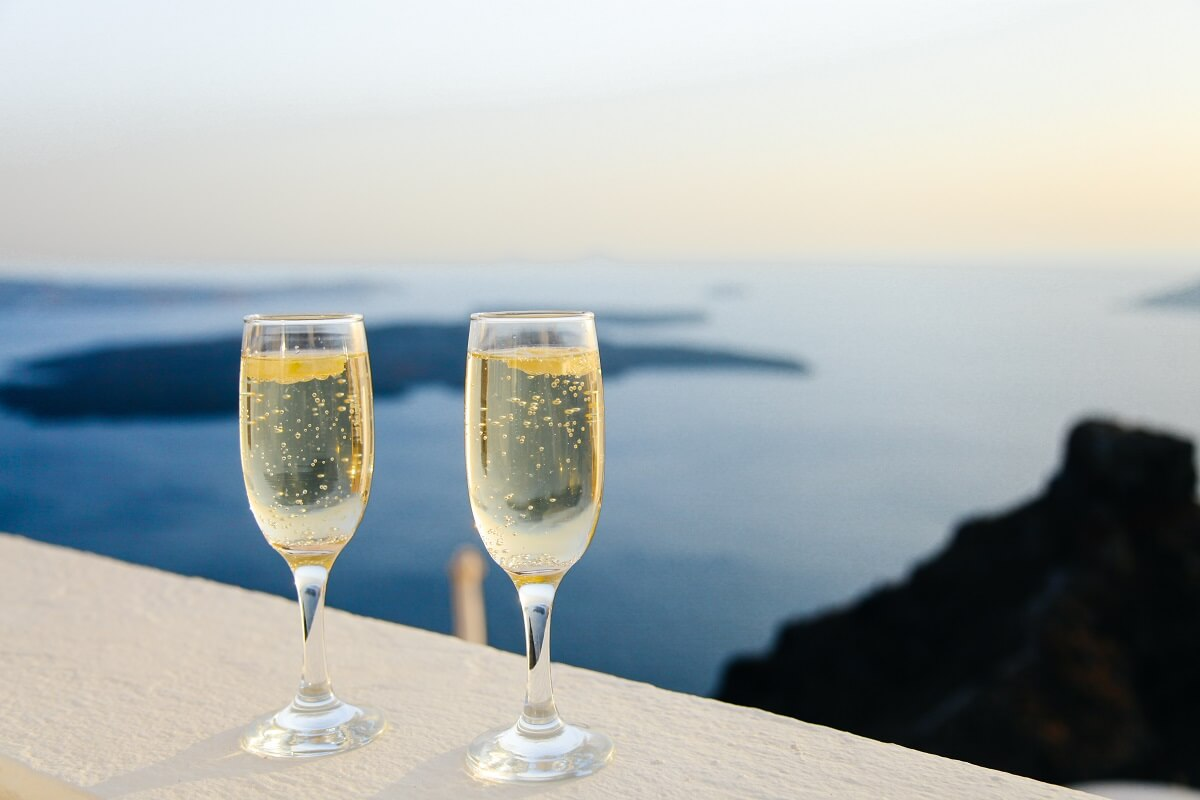 two champagne glasses on a balcony overlooking the beach