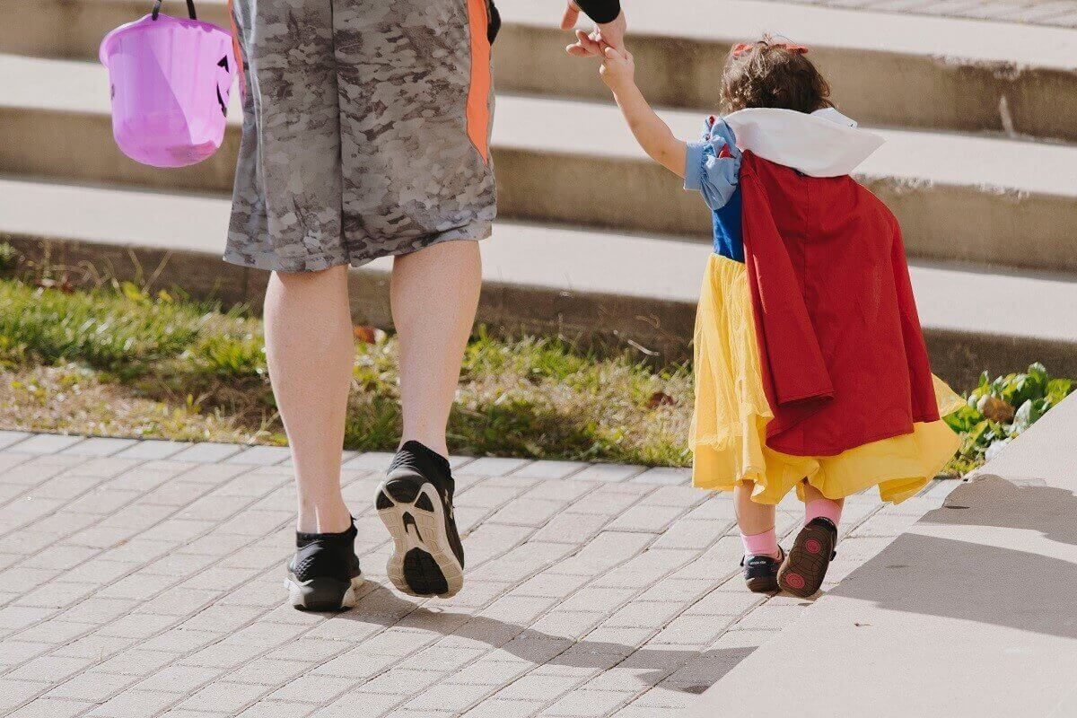 the back of a little girl in a Snow White Costume holding an adult's hand